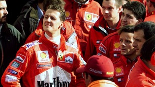 Michael Schumacher surrounded by Ferrari team members and mechanics