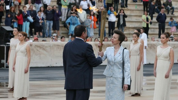 The Princess Royal is handed the torch during the ceremony.
