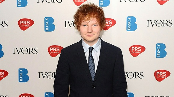 Ed Sheeran celebrates an Ivor Novello award.