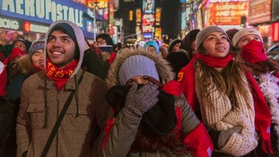 Revellers try to keep warm as they prepare for the New Year's Eve Ball to drop in Times Square.