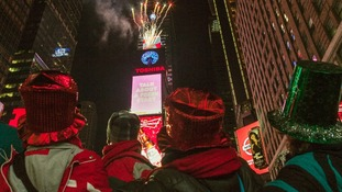 People look towards fireworks exploding from Times Square's New Year's Eve Ball.