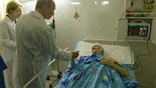 Russia's President Vladimir Putin (front) meets a survivor of one of two bombings in Volgograd.