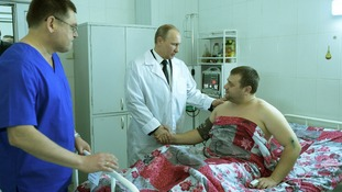 Russian President Vladimir Putin shakes hands with one of the survivors.