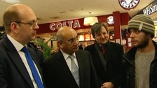 Keith Vaz MP (second from L) greets a Romanian passenger at Luton Airport