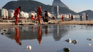 Workers clean the beach of Copacabana after New Year's celebrations - but how clean is the water?