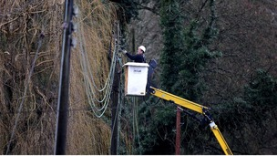 A workman repairing electricity lines near Reigate in Surrey.