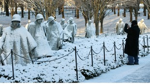 A man photographs the Korean War Veterans Memorial after a heavy snow storm in Washington.