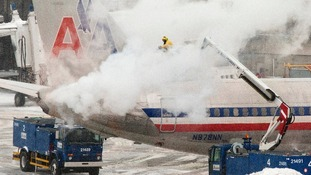 An American Airlines crew member sprays de-icing solution on a plane.