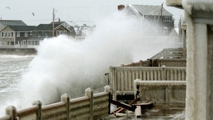 Waves crash in to a house covered in frozen spray in Massachusetts.