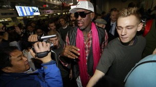 Dennis Rodman (C) is surrounded by journalists as he arrives at the Beijing Capital International Airport to leave for Pyongyang
