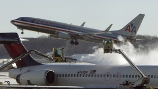 A plane is de-iced at Reagan National Airport in Washington