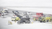 Emergency service vehicles surroud the wreckage of the plane at Aspen Airport