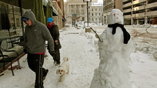 A couple walks their dog past a snowman near the State Capitol building in Indianapolis, Indiana