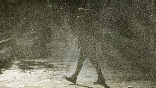 A woman walks through a gust of blowing snow in frigid cold temperatures though downtown Chicago, Illinois