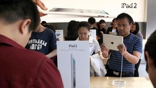 Customers look at the iPad 2 during the launch in China in 2011.