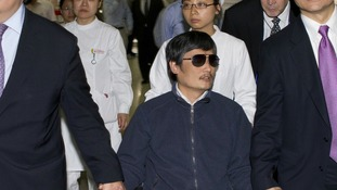 Chen Guangcheng sitting in a wheelchair as he is accompanied by US Ambassador to China Gary Locke at a hospital in Beijing on May 5.