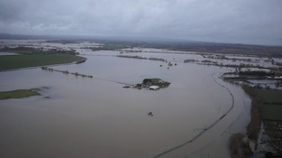 The farm, seen in the centre of the picture, has been completely surrounded by floodwater.