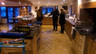 Mike and Jenny Curtis, whose house has flooded for the second time in as many years, show me around