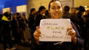 A woman holds a hand-made sign outside the Nantes concert venue.