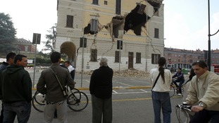 People gather on a street in front of the damaged Town Hall building