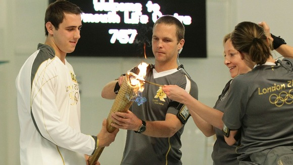 Jordan Anderton holds the torch as it is lit at the start of Day 2 of the Olympic Torch Relay, at the Life Centre in Plymouth