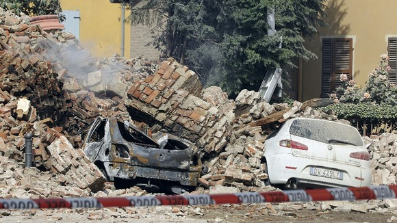 Destroyed cars are seen in the rubble after an earthquake in Finale Emilia