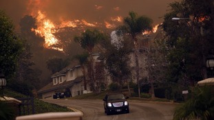 A car drives away from the Colby Fire in hills above Glendora, California