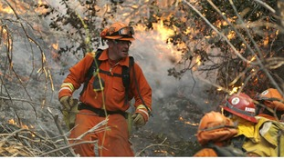 A fire crew climbs a hill at the Colby Fire
