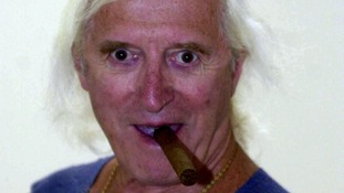 Jimmy Savile with a cigar in his mouth.