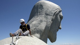 A worker inspects the Christ the Redeemer statue