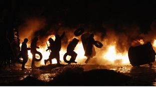 Pro-European protesters throw tyres into a fire during street violence