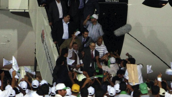 Abdelbasset al Megrahi walks down the stairs upon his arrival at airport in Tripoli August 20, 2009