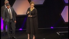 Adele collects one of her awards.