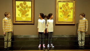 Two sets of twins stand next to the pair of sunflower paintings created by Vincent Van Gogh