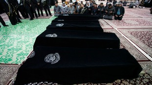 Mourners pray near the coffins of victims killed by a bomb attack at a Shi'ite Muslim village near the Iraqi city of Baquba