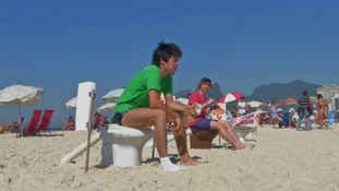 A protester eats his lunch on a toilet on the beach.