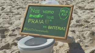A protester's sign reads: 'Bacteria are going to invade you beach'