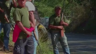 Armed men on the side of a road in Mexico.