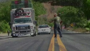 Armed men stop cars on a road in Mexico.