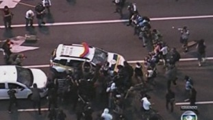 Protesters attack a police car.