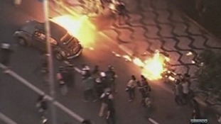 A burning car is driven through the streets.