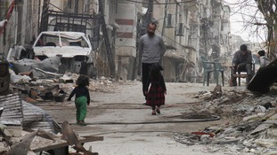 Civilians stand along a street lined with rubble in the besieged area of Homs