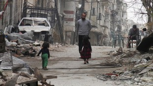 Civilians stand along a street lined with rubble in the besieged area of Homs.