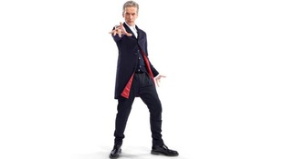 Peter Capaldi wearing a dark blue Crombie coat with red lining, dark blue trousers, a white shirt and Doc Martins.
