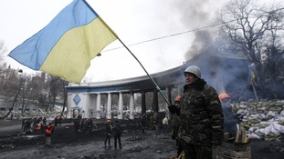 An anti-government protester waves a Ukranian flag