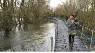 A woman walks along a temporary floating pontoon