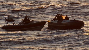 A US crew on board a Royal Navy vessel (L) apprehend the drug smugglers