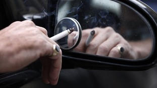 A man smokes a cigarette as he sits in his car.