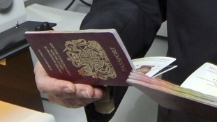 A British passport held in a hand.