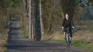 woman on bicycle on country lane
